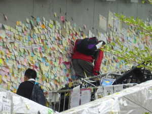 People clamber over the barricades to add to the sticky-note messages